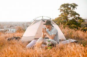 Young man enjoying his food while he camping